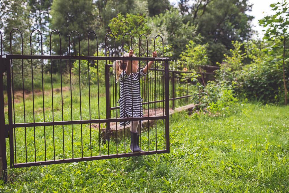 dziecko bawi sie w ogrodzie